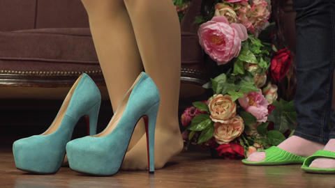 Closeup of slim female legs trying to put on too small size tight high heel blue shoes with red Live Action