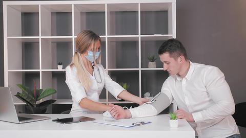 Pressure measurement. A female doctor measures blood pressure using a pressure Live Action