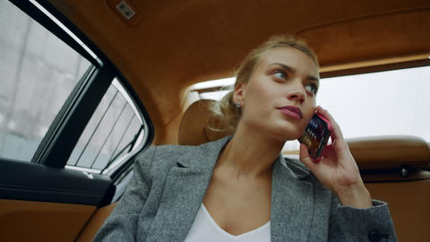 Portrait of female riding at backseat at car. Woman calling mobile phone at car Live Action