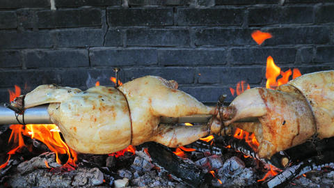 Chicken roasted on spit being grilled over the bright glowing beech wood coals. Turning whole Live Action