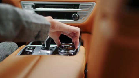 Closeup woman hand using control knob in car. Female using car joystick Live Action