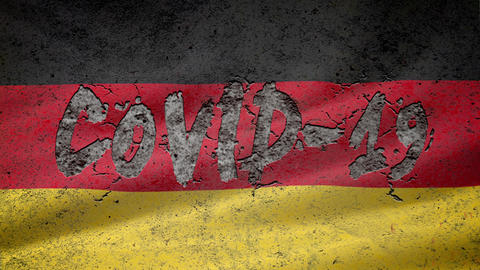 """On the textured concrete wall with the German flag appears the inscription: """"COVID-19'', concrete Live Action"""