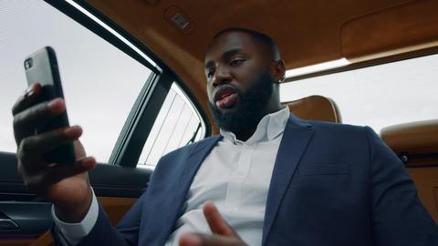 Closeup african man having video call at car. Business man talking phone at car Live Action
