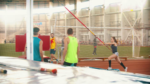 Young people on the pole vault training on indoors stadium Live Action