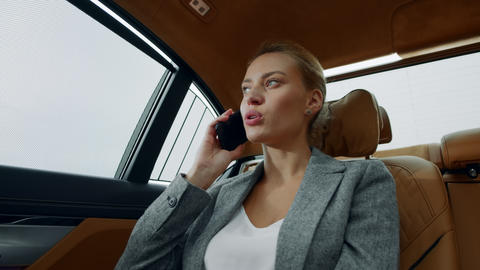 Closeup relaxed businesswoman calling mobile phone in luxury car Live Action