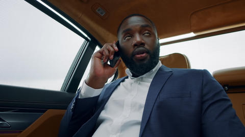 Cheerful african man calling phone at car. Afro businessman smiling at vehicle Live Action