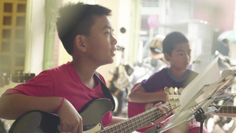 Music School in Phnom Penh, Cambodia, Asia. Student learn to play the guitar Live Action