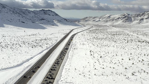 Aerial view above traffic, snowy mountain, Icy, snowy landscape in distance Live Action