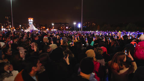 music fans with cellphones watch show in winter evening Live Action
