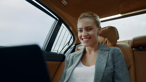 Successful businesswoman enjoying success in car. Business woman looking laptop Live Action