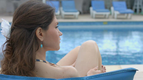 Lonely young female sitting near swimming pool, serious face Footage