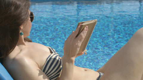 Pretty lady reading book, sunbathing near swimming pool, leisure Footage