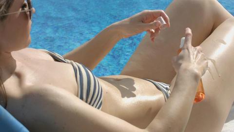 Woman in bikini lying near pool, applying tanning spray on hips Footage