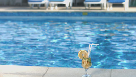 Cocktail on the swimming pool deck. Summer, vacation, lifestyle Footage