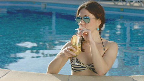 Young woman enjoying long drink in swimming pool, relaxation Footage