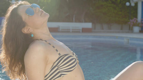 Relaxed woman enjoying stay by the pool, tanning, smiling at cam Footage