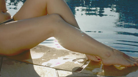 Attractive female legs playfully splashing water out of the pool Footage