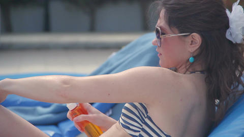 Beautiful young woman in sunglasses using sunscreen on beach Footage