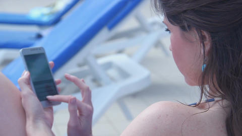 Closeup of young brunette lady texting, sending sms, using phone Live Action
