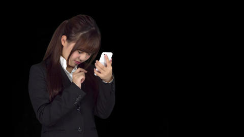 Disappointed young Japanese business woman texting iphone Live Action