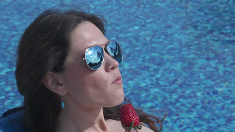 Sexy girl eating strawberry by swimming pool, hot model teasing Footage