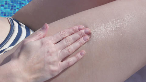 Woman on beach applying spf skincare lotion, rubbing her body Live Action