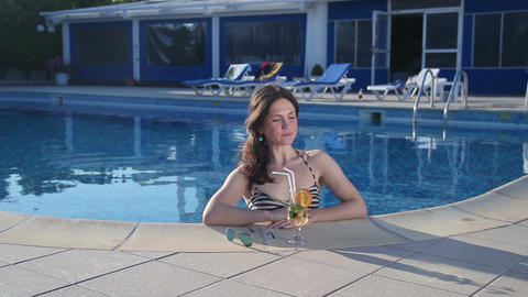 Beautiful single woman enjoying relax, drinking in swimming pool Footage