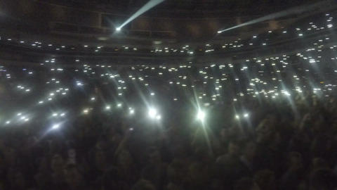 Crowd of fans waving phones in darkness. Lights sparkle during popular slow song Footage