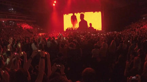 Crowd watching, filming great video background on big stage display at concert Footage