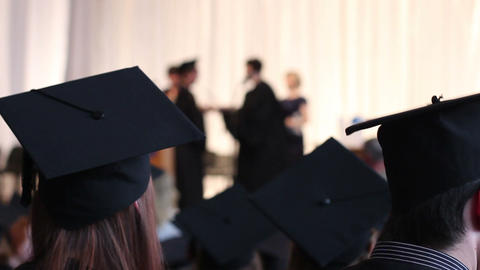 Young people in black academic caps, gowns. Hope for successful career in future Live Action