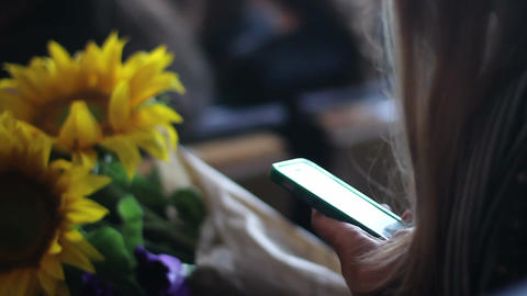 Girl with flowers browsing websites on smartphone at airport, railway station Live Action