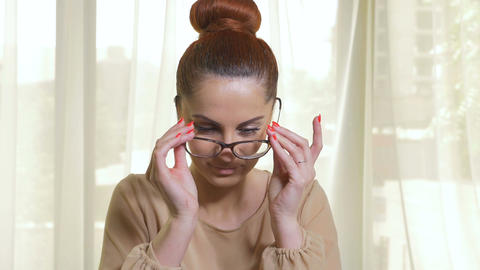 Beautiful woman putting on a pair of modern glasses Footage