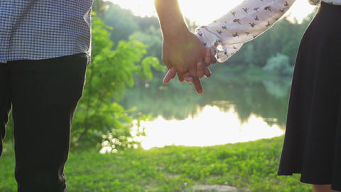 Close-up of couple holding hands at sunset and walking together Footage