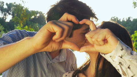 Close-up of young couple making a heart shape at sunset and kissing Footage