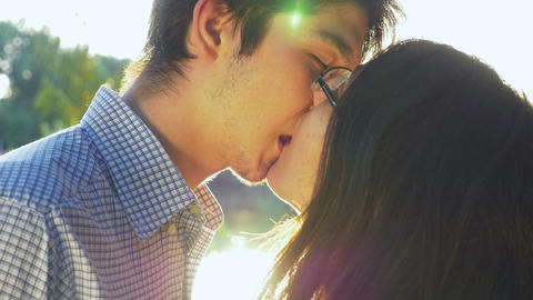 Close-up of loving couple kissing at sunset and looking into the horizon Footage