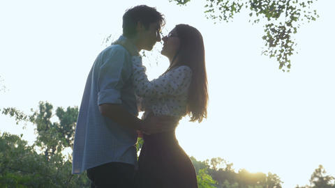 Romantic couple hugging and spinning in the park Footage