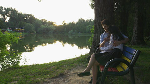Romantic couple walking in the park and sitting on a bench Footage