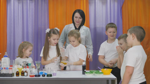 Chemical experiments for children. Children shake a transparent flask with a Live Action