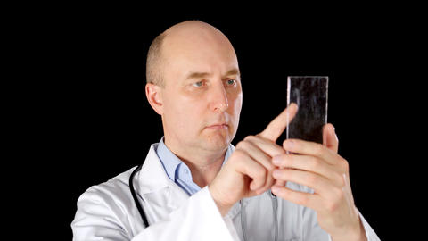 Doctor using touchscreen on transparent smartphone on black background. Medical Live Action