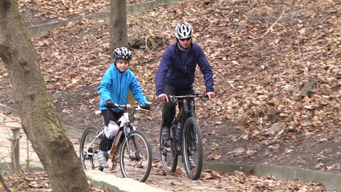 Father and son ride a bike in the park. Paternity. Happy childhood. Slow motion Live Action