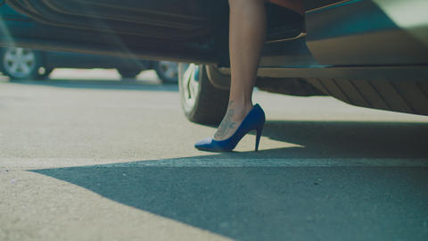 Slim female legs in high heels getting out of car Live Action