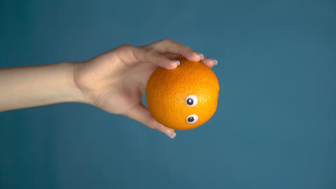 Orange with eyes in a woman hand close up. Orange looks around on a blue Live Action
