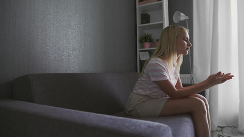 Upset woman sitting on couch alone remembers about quarrel with boyfriend feels Live Action