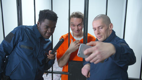 Jailers take selfies with prisoners. Medium shot Live Action