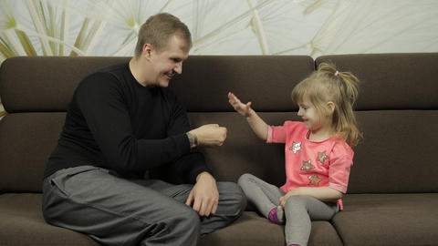 Father and little daughter playing rock paper scissors on sofa. Leisure game Live Action