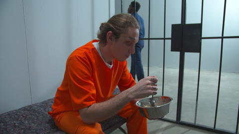 Prisoner eating lunch in his cell. Medium shot Live Action