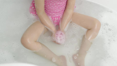 Hands of girl puts bath bomb to water. Ball of bath salt dissolves in water Live Action