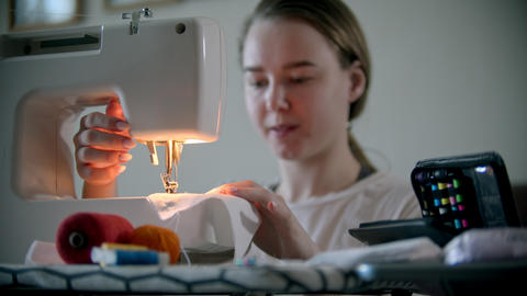 Young woman designer sewing decorative mask using a sewing machine Live Action
