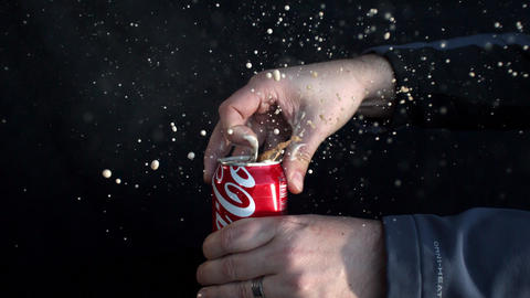 Slow motion of soda can opening and spraying as tab is being pulled Live Action