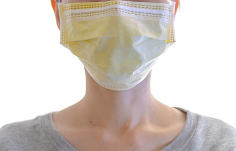 Close up of woman wearing surgical mask on her face on white for protection against contagious or Photo
